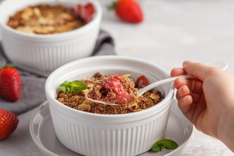 Sommerfrühstücks-Erdbeerkrümel in der Kinderhand Minibeere Ca lizenzfreies stockfoto