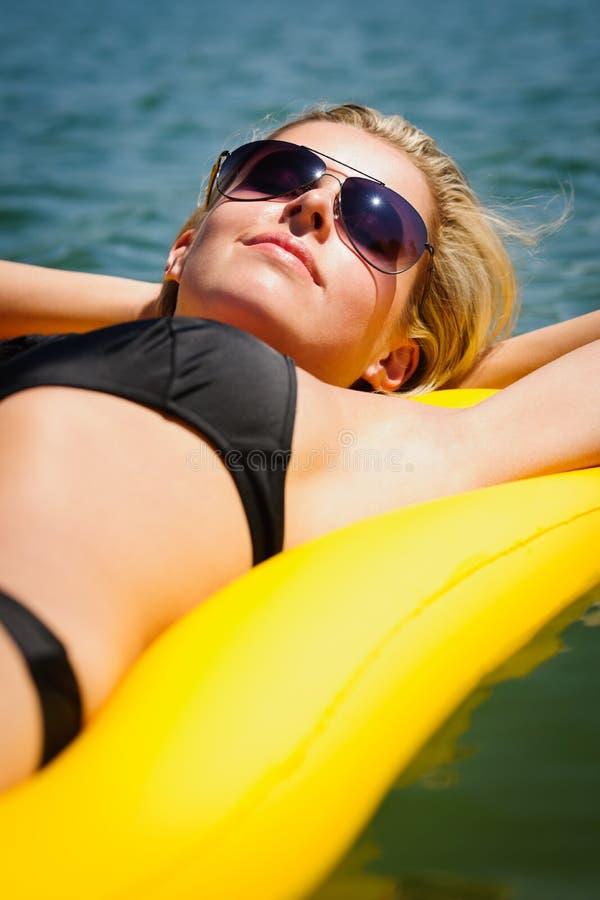 Sommerfrau entspannen sich auf sich hin- und herbewegender Matratze des Wassers lizenzfreies stockfoto