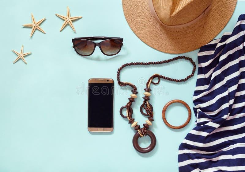 Sommerfrauen ` s Strandzubehör für Ihren Seefeiertag: Strohhut, Armbänder, Sonnenbrillen, Perlen, streifte Kleid, Telefon stockfotos