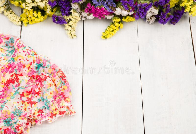 Sommerfrauen stellten mit Kleid und bunten Blumen auf weißem hölzernem ein stockfoto