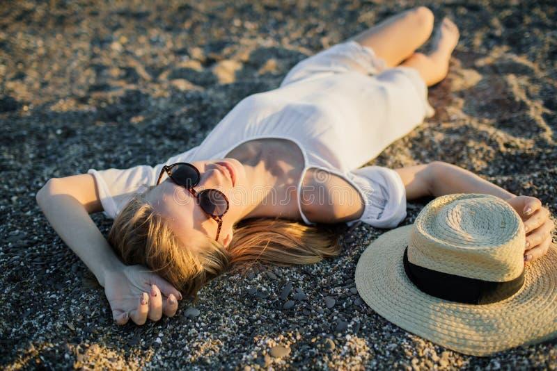 Sommerfrauenentspannung, liegend im Sand am Strand lizenzfreies stockbild