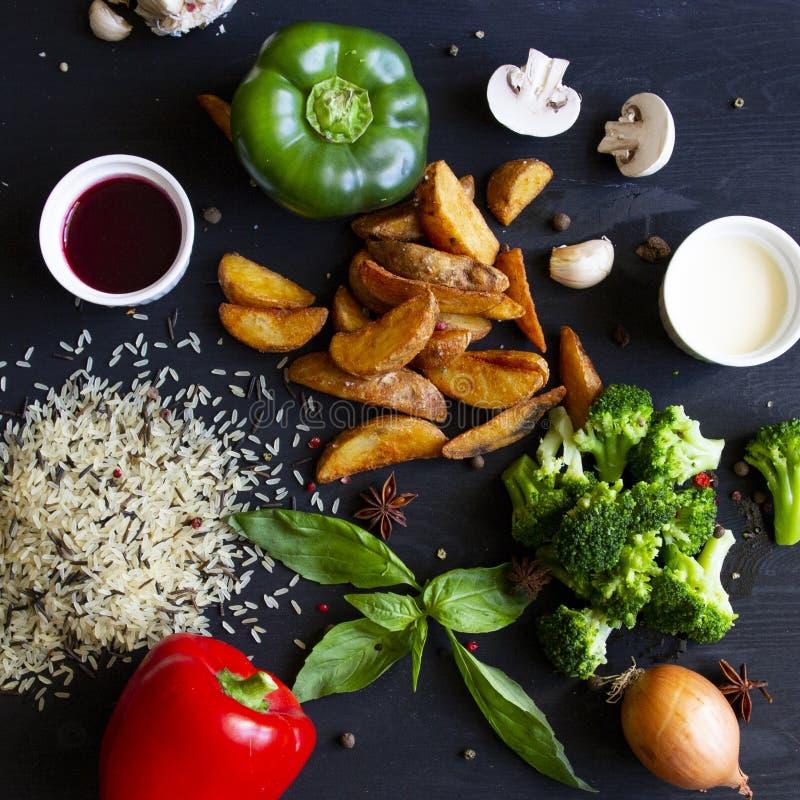Sommergemüse auf schwarzem hölzernem Hintergrund Roter und Brokkolireis des grünen Paprikas und gebratene Kartoffeln lizenzfreie stockbilder