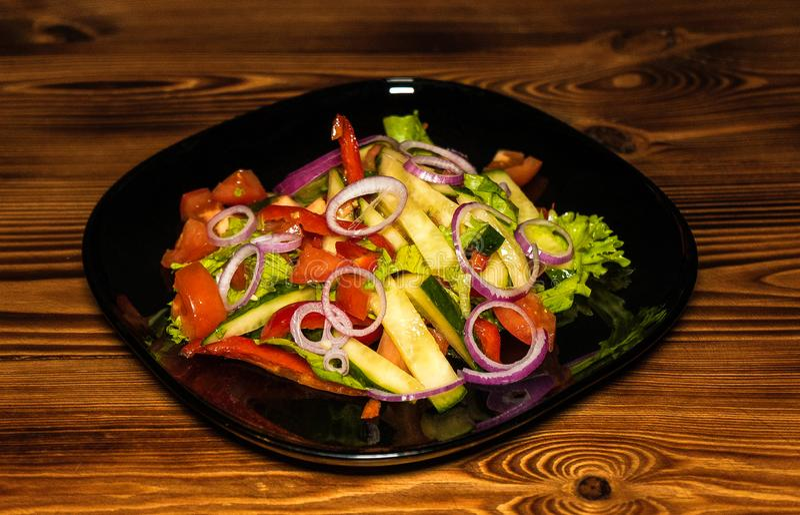Sommergemüsesalat von Zwiebeln, Gurken, Tomaten und Grüns, kochend lizenzfreie stockfotografie