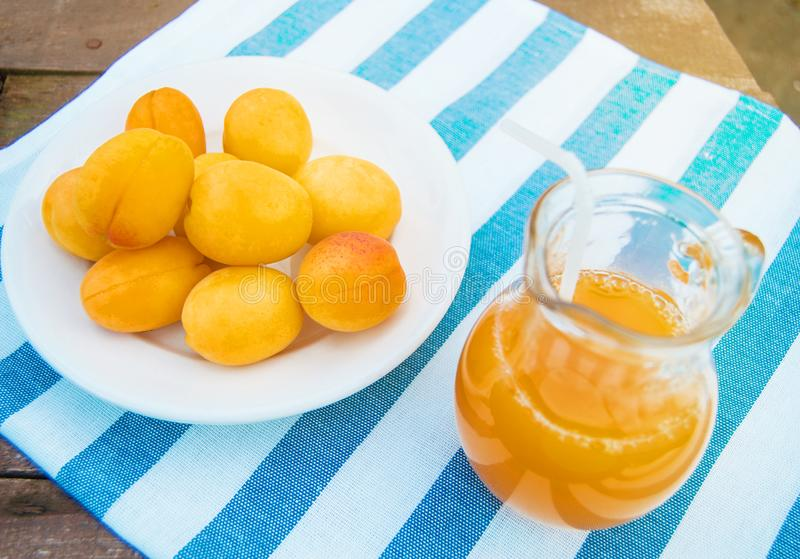 Sommergetr?nk und Frucht-frischer Aprikosensaft in einem Glaskrug und in reifen Aprikosen auf einer Serviette, drau?en an einem s stockfotografie