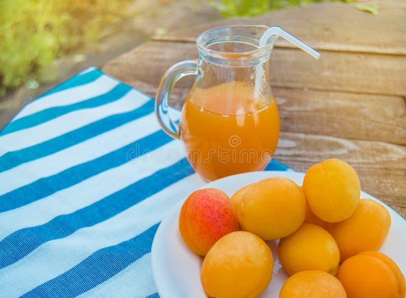 Sommergetr?nk und Frucht-frischer Aprikosensaft in einem Glaskrug und in reifen Aprikosen auf einer Serviette, drau?en an einem s lizenzfreies stockfoto