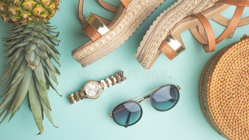 Sommerhintergrund mit einer Weidenmodetasche und Sommerschuhe der Frauen und Sonnenbrillen, Uhren Sommermode, das Konzept von stockfotos