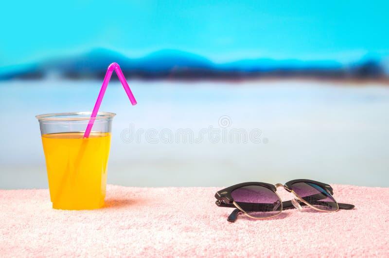 Sommerhintergrund mit gelbem Cocktail und Sonnenbrille auf Tuch auf dem Strand Schöner unscharfer Paradiesmeerblick stockfoto