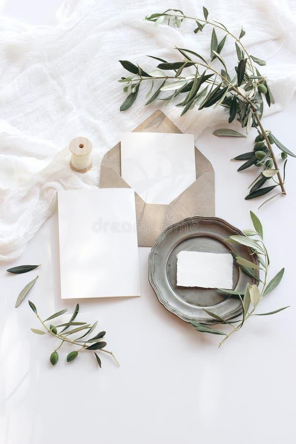 Sommerhochzeitsbriefpapier-Modellszene Leere Grußkarten, Umschlag, silberne Platte der Weinlese, Ölzweige und Band lizenzfreie stockfotos