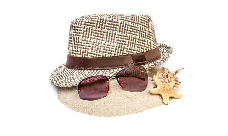 Sommerhut mit Sonnenbrille und Muscheln auf Sandhaufen Lokalisiert auf Wei? lizenzfreie stockfotografie