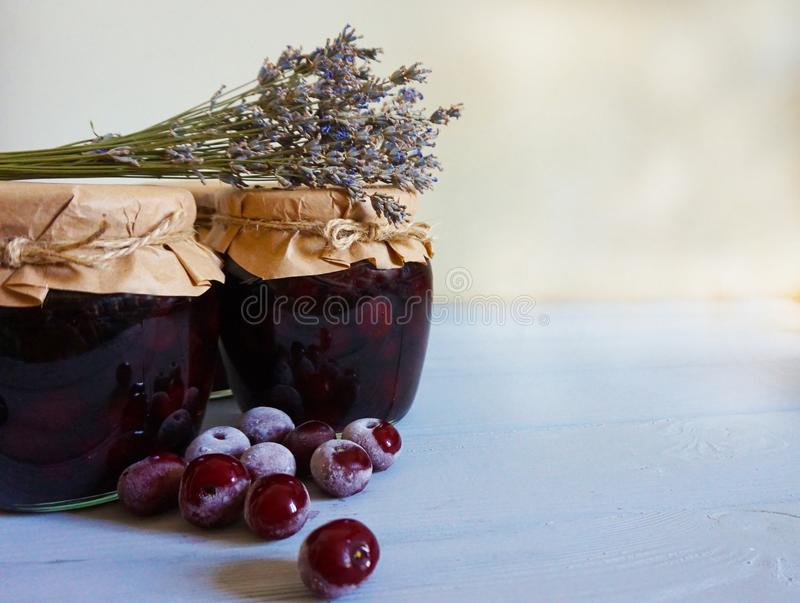SommerKirschmarmelade gegen gefrorene Beeren stockbild