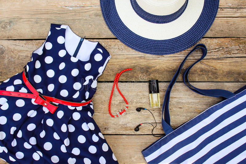 Sommerkleidung und -Zubehör: Kleid, Geldbeutel, Hut, Kopfhörer, Parfüm, Handtasche und Perlen stockfoto
