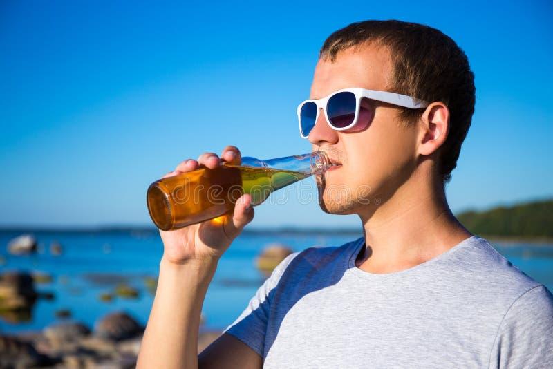 Sommerkonzept - trinkendes Bier des gutaussehenden Mannes auf dem Strand stockbild
