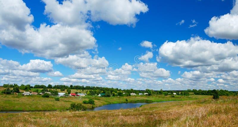 Sommerlandlandschaft mit Fluss und Dorf auf die Oberseite des Hügels stockbilder