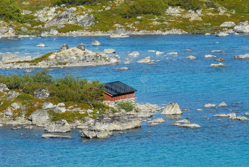 Sommerlandschaft mit dem Rot malte Häuschen an einem Seeufer in ländlichem Norwegen stockbild
