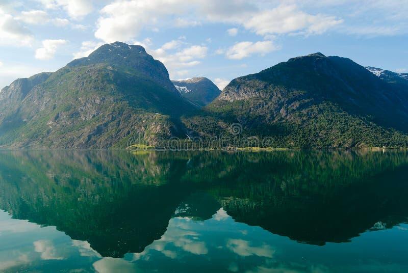 Sommerlandschaft mit den Bergen und Himmel, die im Fjord in ländlichem Norwegen sich reflektieren stockfoto