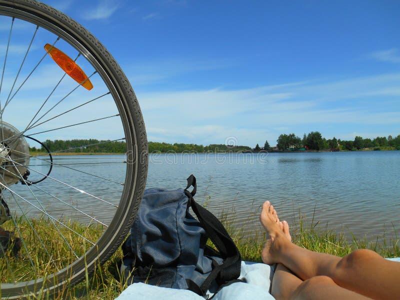 Sommerlandschaftsfahrrad whell und barfüßigbeinmädchen, die auf einem Hintergrund des blauen Himmels des Sees stillstehen stockbild