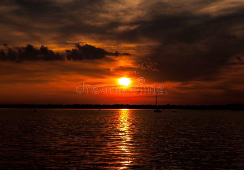Sommerlandschaftsszenischer brennender Sonnenuntergang über ruhigem Fluss stockfotografie