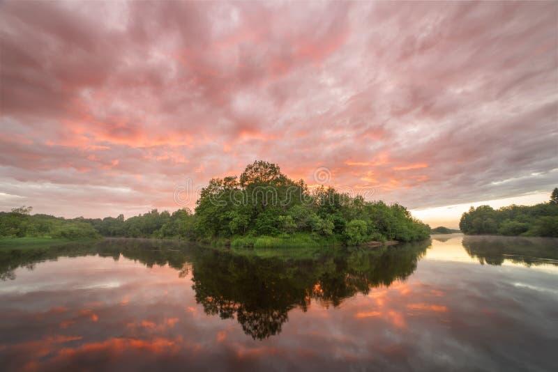 Sommerlandschaftsszenischer brennender Sonnenuntergang über ruhigem Fluss stockbild
