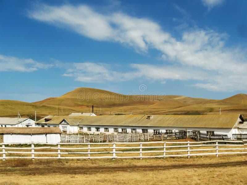 Sommerlandschaftsweißer Stall mit Zäunen, gelbe Hügel lizenzfreies stockbild