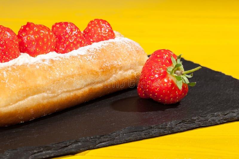 Sommerlebensmittel Erdbeersahnedonutkuchen auf hellem gelbem backgr lizenzfreie stockfotos