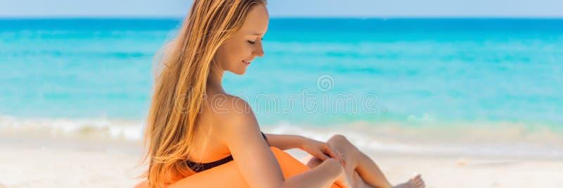 Sommerlebensstilporträt des hübschen Mädchens sitzend auf dem orange aufblasbaren Sofa auf dem Strand von Tropeninsel Entspannung lizenzfreie stockfotos