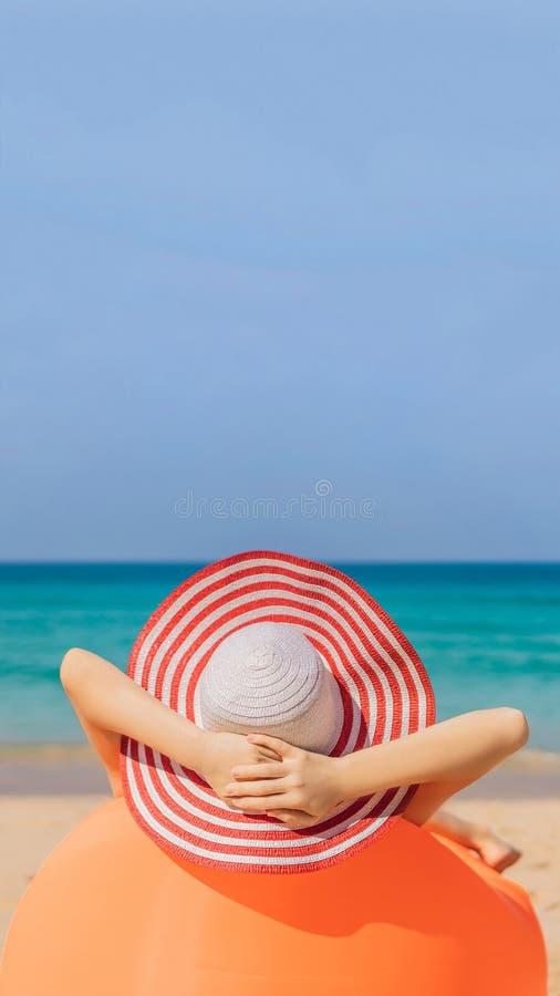 Sommerlebensstilporträt des hübschen Mädchens sitzend auf dem orange aufblasbaren Sofa auf dem Strand von Tropeninsel Entspannung stockfoto
