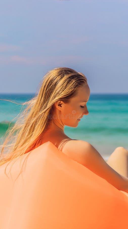 Sommerlebensstilporträt des hübschen Mädchens sitzend auf dem orange aufblasbaren Sofa auf dem Strand von Tropeninsel Entspannung stockbilder