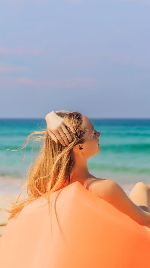 Sommerlebensstilporträt des hübschen Mädchens sitzend auf dem orange aufblasbaren Sofa auf dem Strand von Tropeninsel Entspannung stockbild