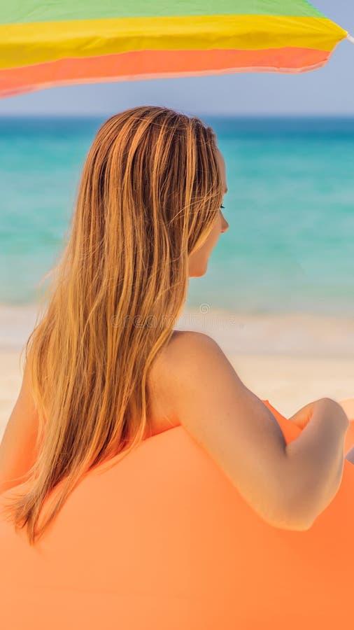 Sommerlebensstilporträt des hübschen Mädchens sitzend auf dem orange aufblasbaren Sofa auf dem Strand von Tropeninsel Entspannung lizenzfreies stockbild