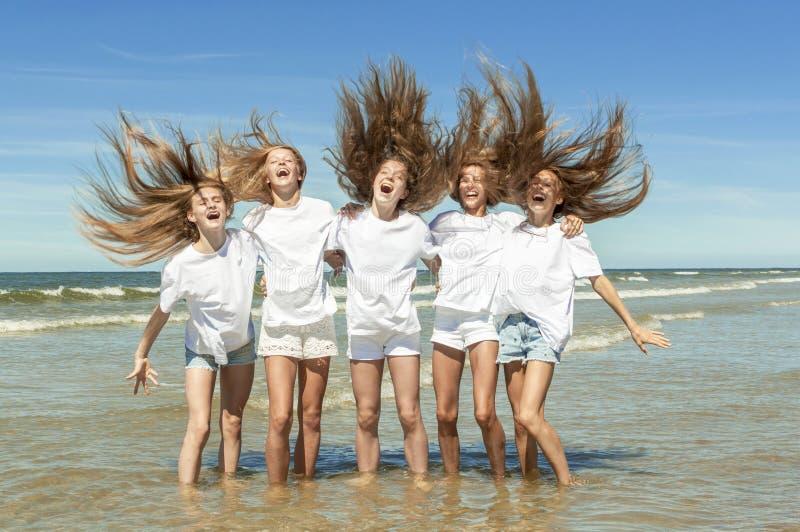 Sommermädchen, die auf Strand spielen stockfotografie