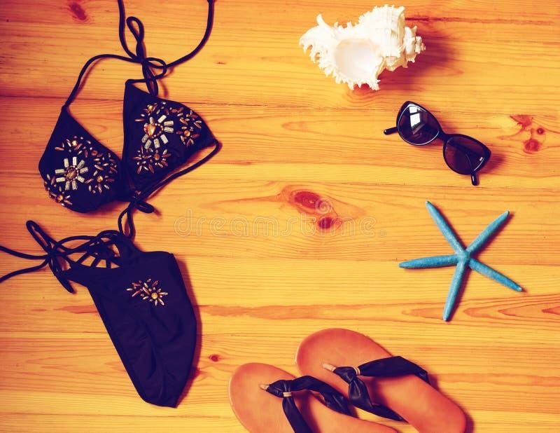 Sommermädchenzubehör auf Draufsicht des hölzernen Hintergrundes getont stockfotografie