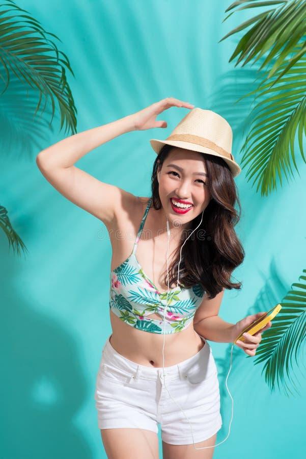 Sommermodemädchen, das über vibrierendem blauem backg steht und lächelt lizenzfreies stockfoto