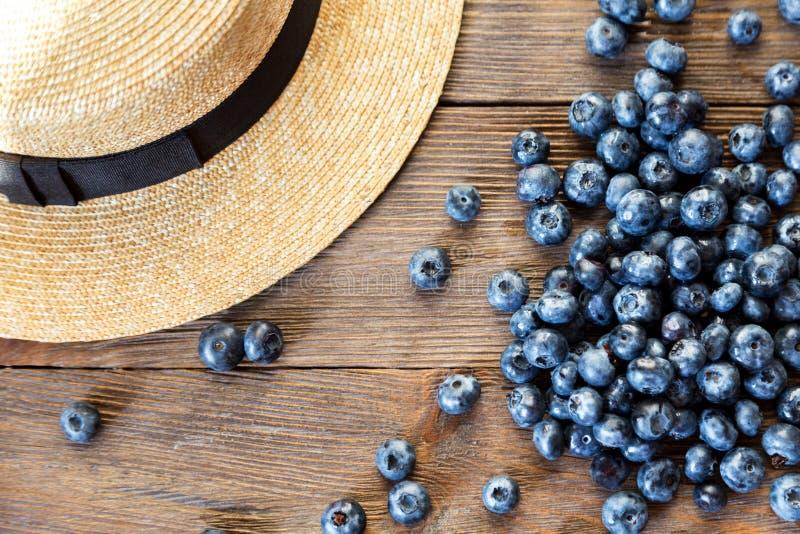 Sommernahaufnahme von Blaubeeren und von Strohhut auf hölzernem Hintergrund der Weinlese lizenzfreie stockfotografie