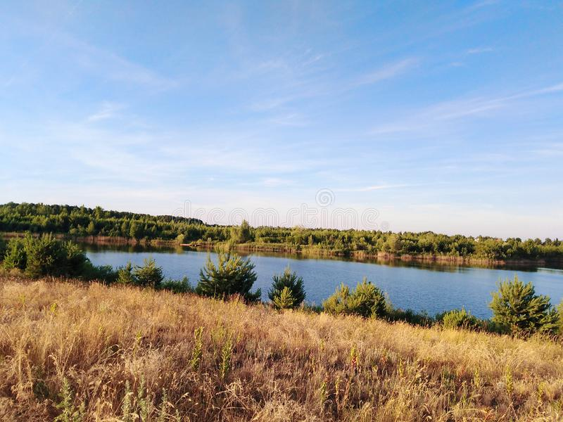 Sommernatur mit einem See Wald und Feld lizenzfreie stockfotos