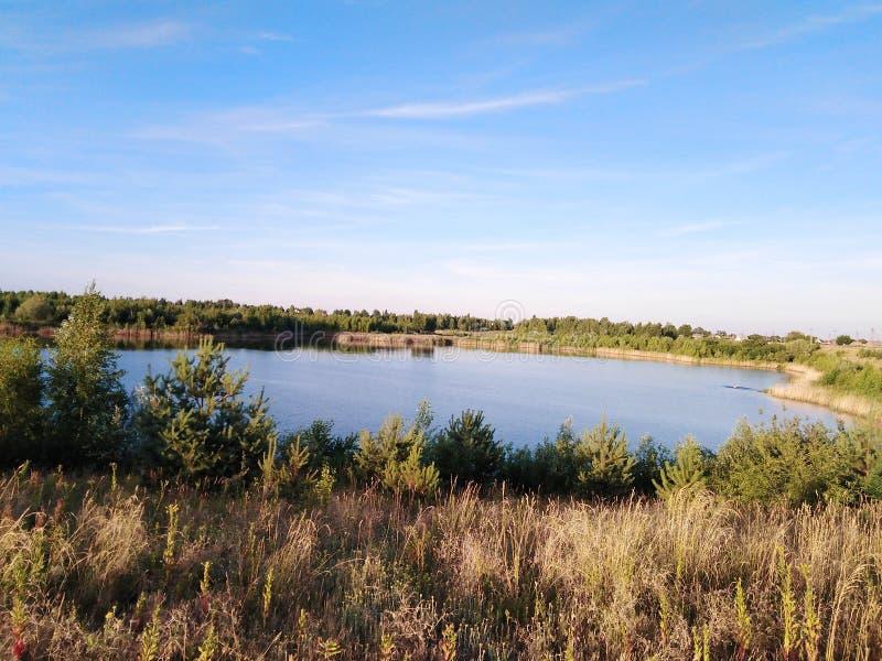 Sommernatur mit einem See Wald und Feld stockfoto