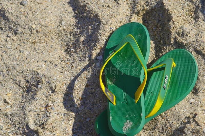 Sommerpantoffel auf dem sandigen Strand stockfotografie
