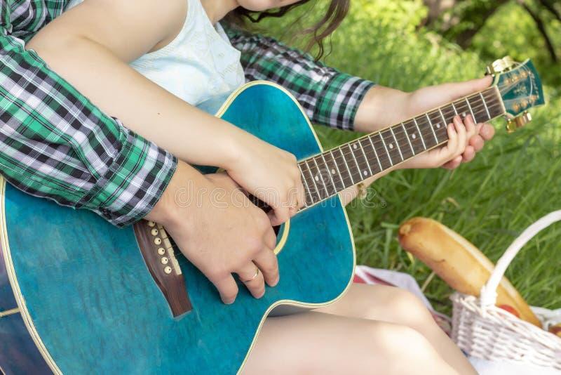 Sommerpicknickkerl unterrichtet Mädchen, Weichheit der Gitarrenliebe zu spielen warme lizenzfreie stockfotografie