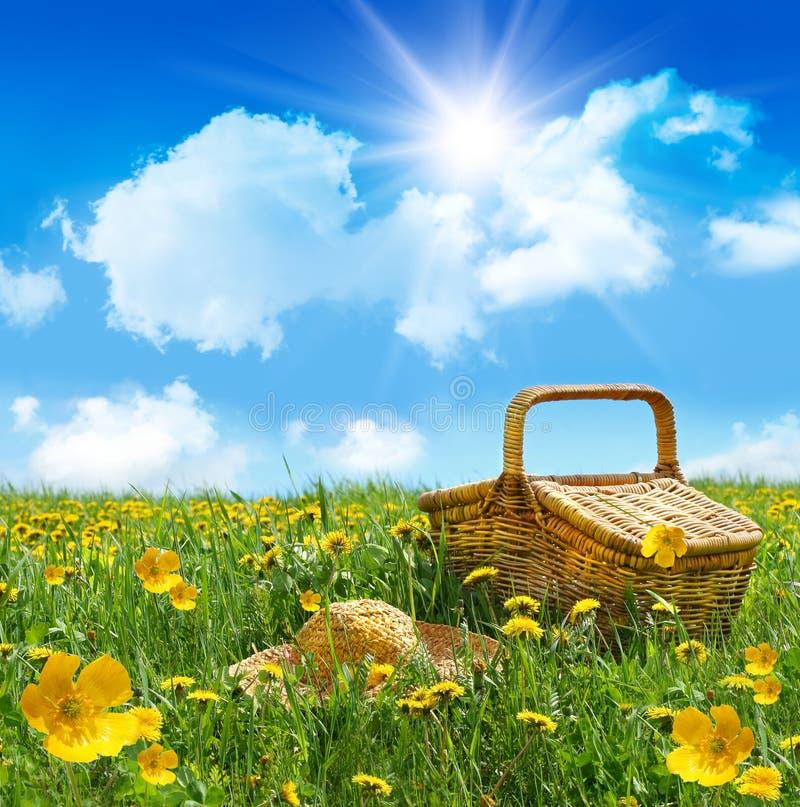 Sommerpicknickkorb mit Strohhut auf einem Gebiet lizenzfreie stockfotografie