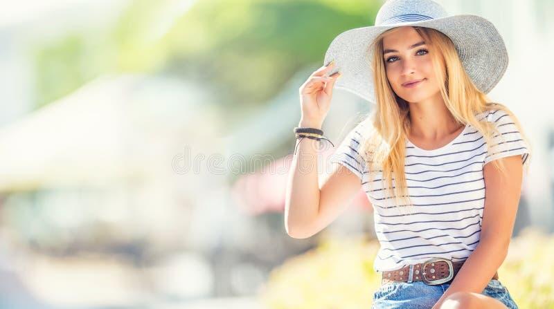 Sommerporträt der jungen Schönheit im Hut, der auf Bank im Park sitzt lizenzfreie stockbilder
