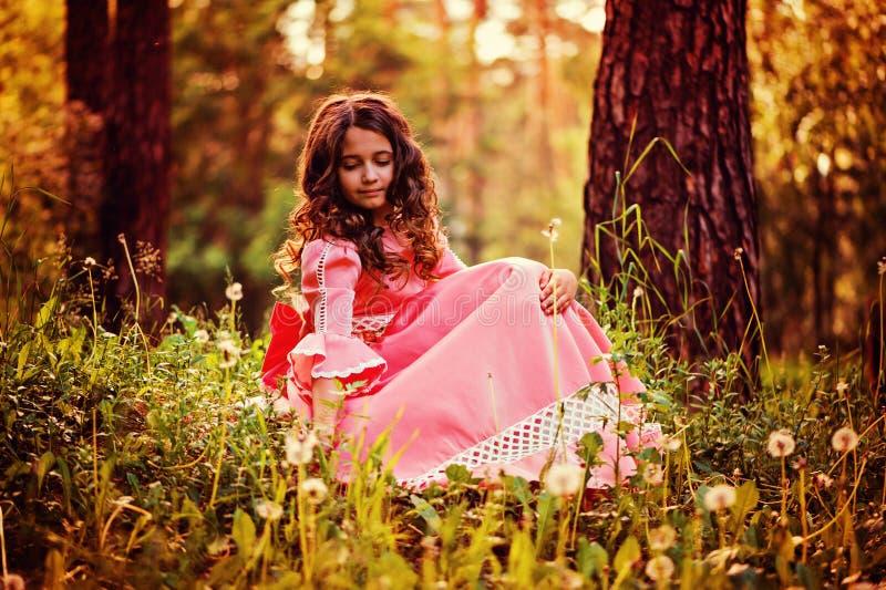 Sommerporträt des gelockten Kindermädchens kleidete im rosa Märchenprinzessinkleidersammelnlöwenzahn an stockfotos