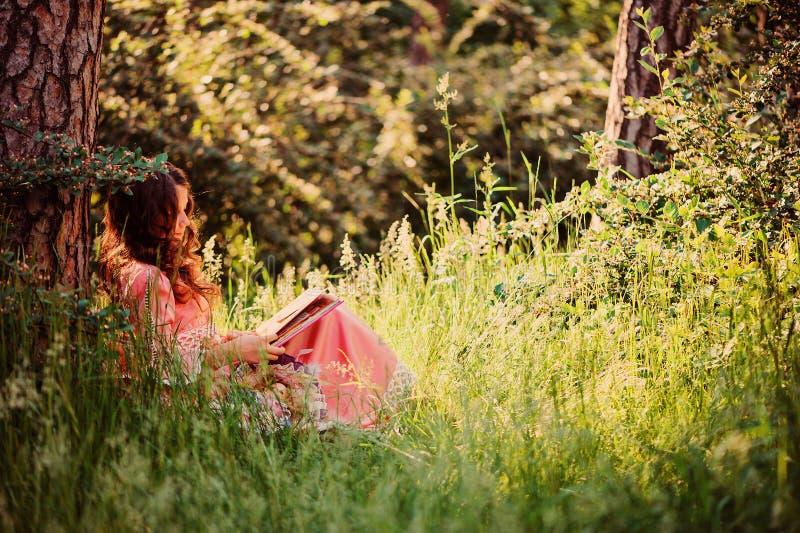 Sommerporträt des glücklichen Kindermädchens kleidete im rosa Märchenprinzessinkleiderlesebuch an stockfotos