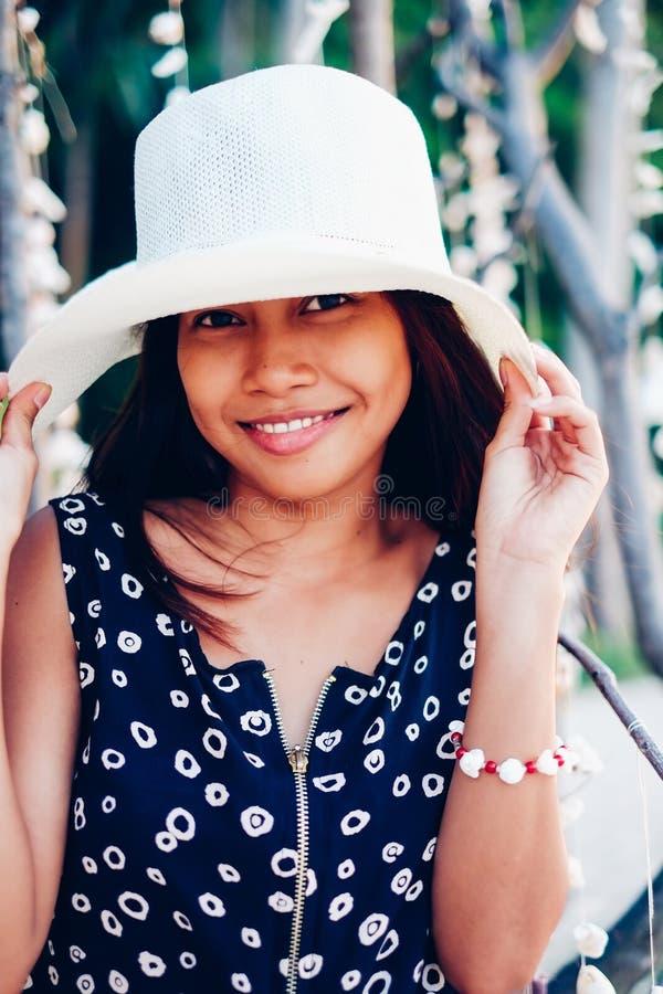 Sommerporträt des schönen jungen asiatischen Mädchens mit Hut auf dem Strand lizenzfreies stockbild