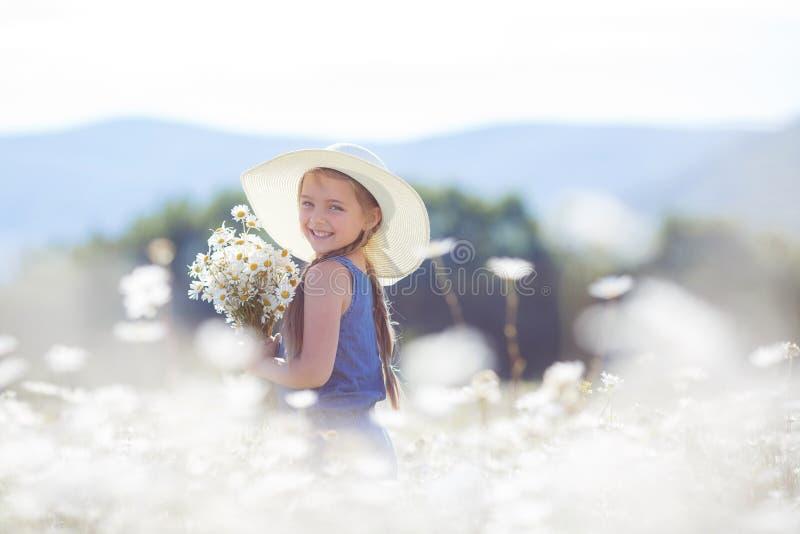 Sommerporträt eines kleinen Mädchens auf einem Gebiet von weißen Gänseblümchen stockbild