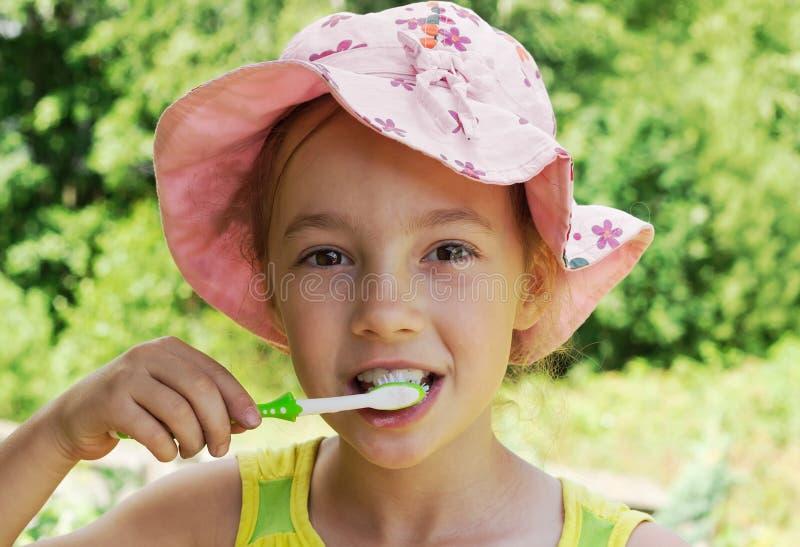 Sommerporträt von bürstenden Zähnen des entzückenden Mädchens stockfoto