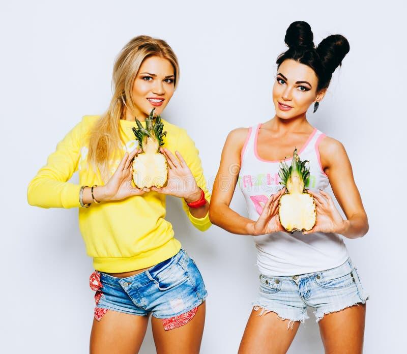 Sommerporträt von zwei netten Freundinnen, Spaß mit Scheibenananas und -c$lächeln habend Zufällige Art, helles Make-up lizenzfreies stockbild