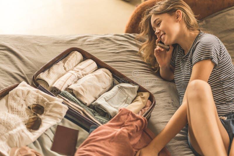Sommerreise und Ferienkonzept, Verpackungskoffer der jungen Frau zu Hause lizenzfreies stockfoto