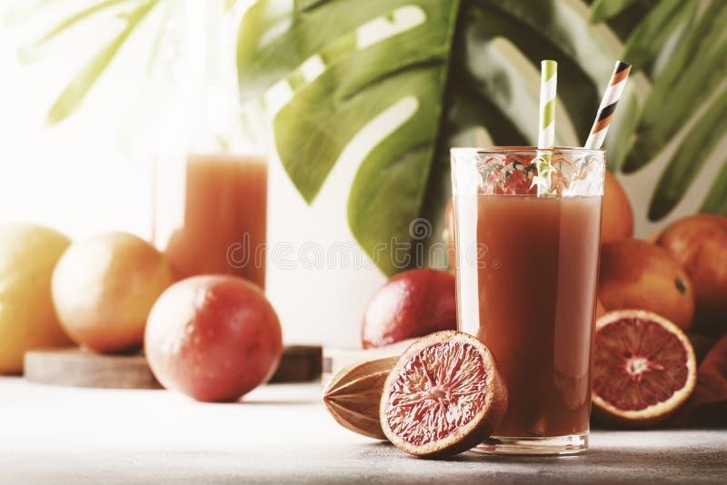 Sommersaft von der roten sizilianischen Orange, grauer Tabellenhintergrund Selektiver Fokus lizenzfreie stockfotos