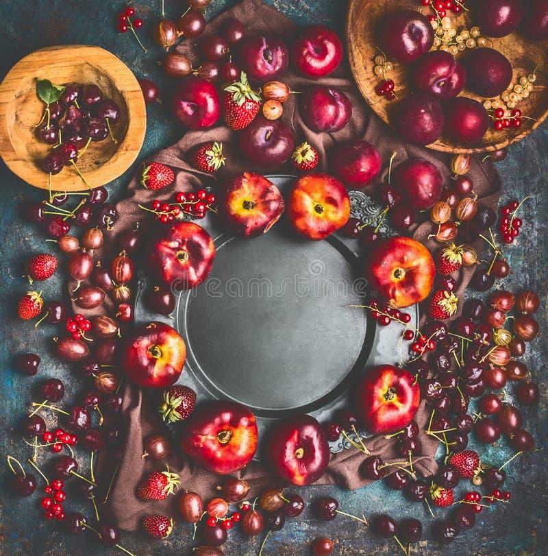 Sommersaisonfrüchte und -beeren ernten Hintergrundrahmen mit Fruchtschüsseln und Gartenblumen um leere Platte lizenzfreie stockfotografie