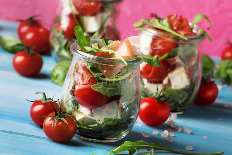 Sommersalat mit Arugula, Weichkäse, Kirschtomaten und Prosciutto in den Glasgefäßen, modischer rosa blauer Hintergrund, selektive lizenzfreie stockfotos