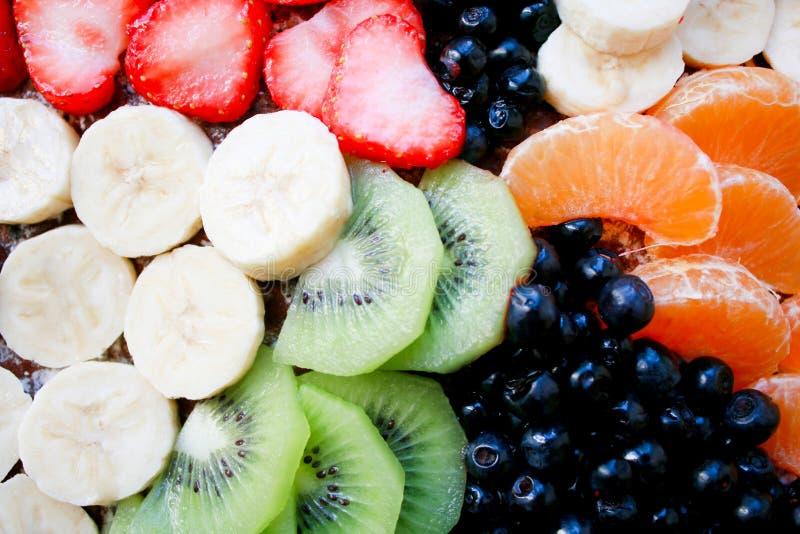 Sommerschwammkuchen mit Bananen, Erdbeeren, Korinthen, Tangerinen, Heidelbeeren und Kiwi Draufsicht horizontal stockfotografie